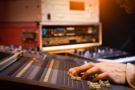 male sound engineer, dj hand working on audio mixing console recording, editing, broadcasting studio
