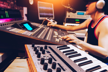 asian male artist, producer, dj mixing a song in recording, editing, broadcasting studio. music production concept