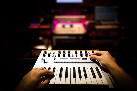 musician, producer, composer, arranger hands playing keyboard synthesizer in recording studio, music production concept