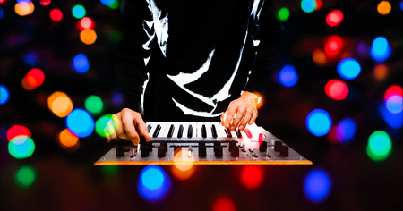 male musician, remixer, dj playing music keyboard synthesizer with colourful bokeh Imagens