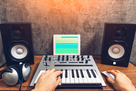 home studio, music production technology concept, male musician hands playing keyboard for arranging a song on tablet computer 스톡 콘텐츠