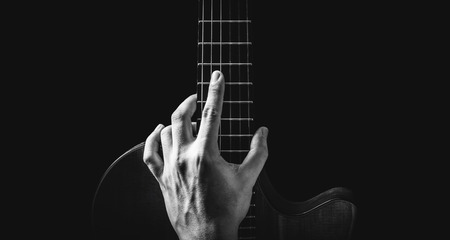 black and white male musician hand posing on guitar, isolated on black, music background Imagens