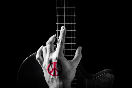red peace symbol tattoo on hand, posing on guitar. isolated on black. music background