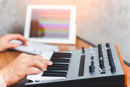 producer hands composing a song or online music education on keyboard and tablet computer