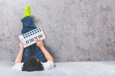 asian man enjoy playing keyboard on bed, music background Stockfoto