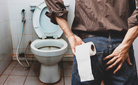 man holding tissue roll in dirty toilet