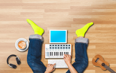 top view of male musician composing a song with tablet computer, keyboard, ukulele, headphone while enjoying coffee on the floor