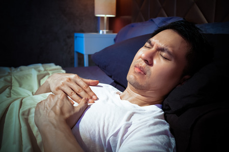 asian man has a heart attack symptoms while sleeping on bed at night