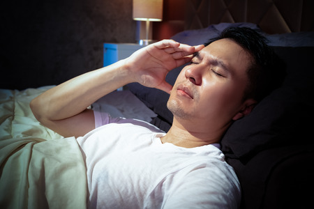 asian man in bed suffering insomnia and headache, thinking about his problem at night