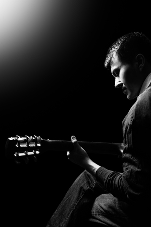 black and white portrait of asian musician playing acoustic guitar on stage Imagens