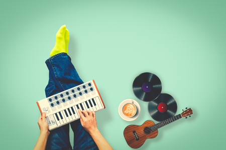 top view of male musician playing keyboard with ukulele, record, cup of coffee on green floor Stockfoto