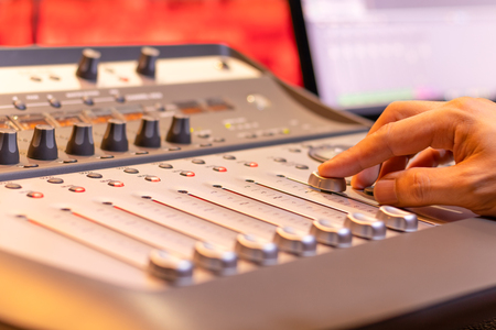sound engineer fingers adjusting volume level fader on digital mixing console. music production, recording, broadcasting, music concept Foto de archivo