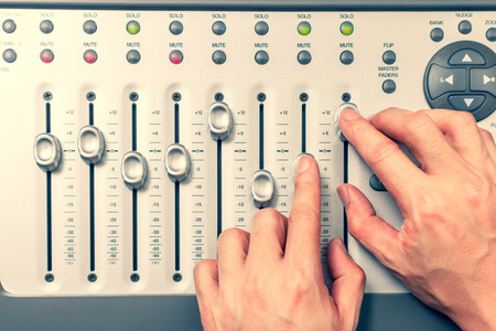 sound engineer hands adjusting volume level fader on digital mixing console. music production, recording, broadcasting, music concept Stockfoto