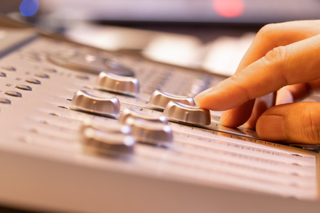 sound engineer fingers adjusting volume level fader on digital mixing console. music production, recording, broadcasting, music concept Stockfoto