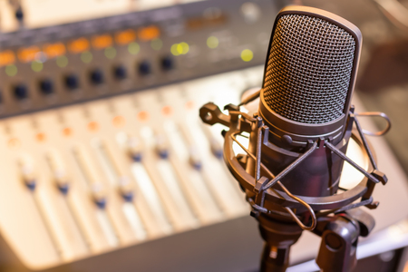 condenser microphone on mixing console background. audio recording concept