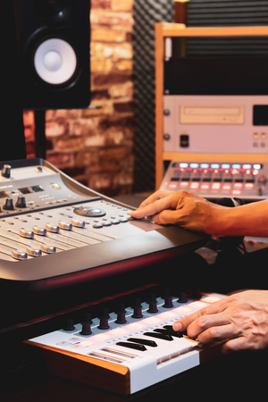 producer hands arranging and mixing music in home studio. music production concept