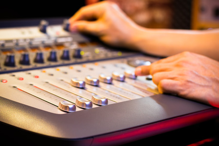 male sound engineer, dj hand working on audio mixing console in recording, editing, broadcasting studio