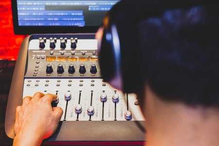 back of male sound engineer working on digital audio mixing console in recording, editing, broadcasting studio. focus on hand