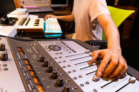asian male professional producer mixing audio tracks on digital sound mixer in home studio. music production concept Stockfoto