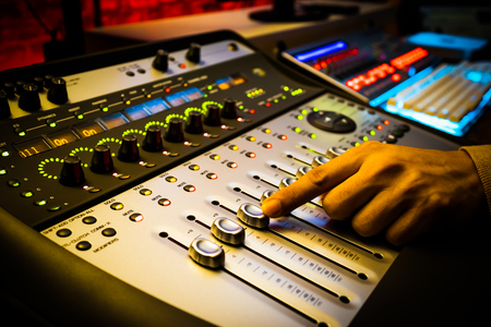 sound engineer, producer hand working on professional recording, broadcasting studio equipment