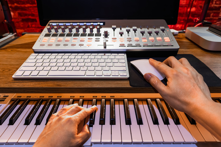 musician hands playing piano for recording a song on computer. music production concept
