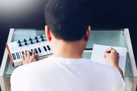 back of asian male songwriter playing music keyboard and writing a song on blank white paper, song writing concept