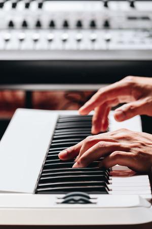 pianist hands playing white piano in recording studio Stockfoto