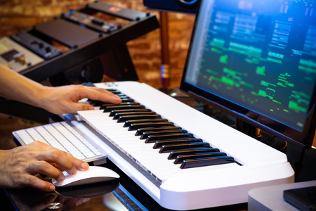 male professional music producer hands arranging a song on midi keyboard and computer in home studio. music production concept Stockfoto