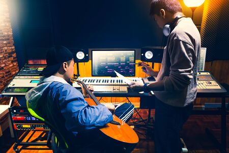 male asian producer consulting with professional guitarist about style of a song to record in recording studio