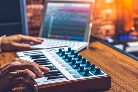 male musician hands arranging a song on midi keyboard and laptop computer. music technology concept Stockfoto