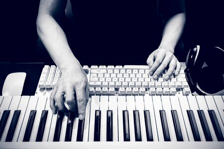 male composer hands playing piano for arranging music on computer