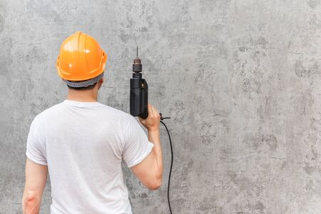 back of asian handyman holding electric drill on cement wall background. home renovation concept Stockfoto