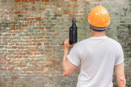 back of asian handyman holding electric drill on old grunge brick wall background. home renovation concept