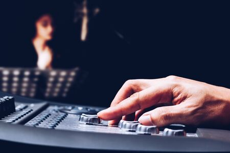 producer fingers adjusting audio level signal on digital sound mixer for recording female voice in studio