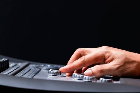 sound engineer fingers adjusting audio level signal on mixing console fader. music production background concept
