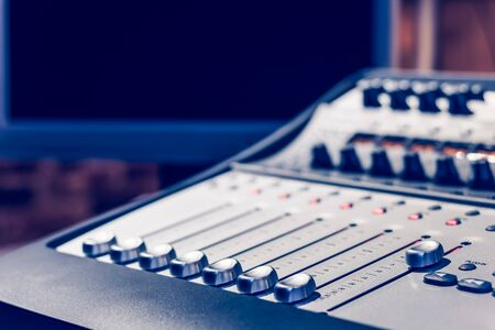 audio mixer console on computer monitor background. recording, music production, broadcasting concept