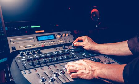 male sound engineer hands mixing a song on professional audio equipment in recording studio Stockfoto