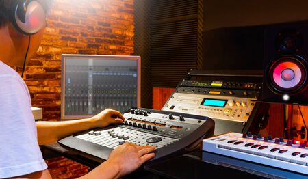 asian sound engineer mixing music in home recording studio. recording, broadcasting, editing, post production concept