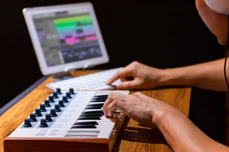 male composer arranging music on midi keyboard and tablet computer in home studio