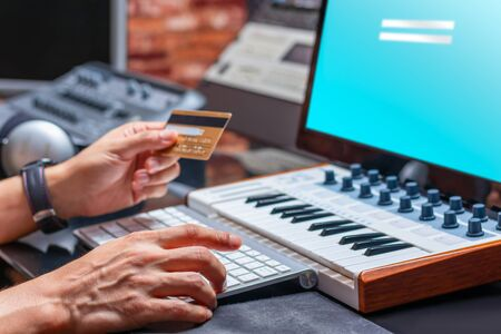 musician hands holding credit card for online shopping in music studio