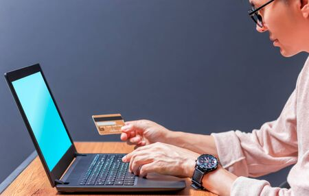 young asian handsome man holding credit card and using laptop computer on dark background. online shopping concept Stockfoto