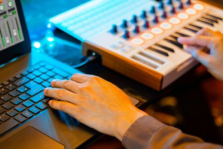 music producer hands composing a song on laptop computer and midi keyboard in home recording studio. music production concept