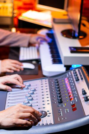 producer and sound engineer hands mixing, recording sound for movie score or advertising jingle in studio. recording, broadcasting, editing, music production concept Stock fotó - 132034892