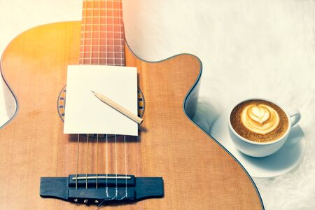 blank notepad and pencil on acoustic guitar with cup of coffee in the morning. song writing concept 스톡 콘텐츠 - 132034552