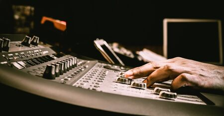 sound engineer hand adjusting audio level on digital mixing console fader in recording, broadcasting studio