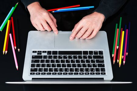 male graphic designer working on laptop computer with color pencils