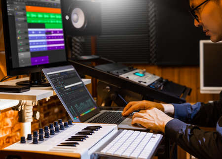 Male producer, musician, composer making a song in home recording studio. Standard-Bild