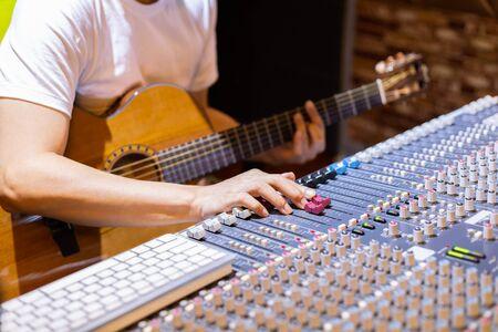 male musician recording acoustic guitar track in sound studio