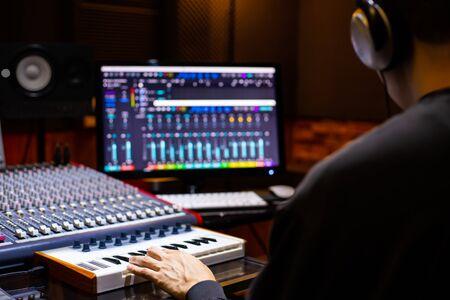 Rückseite des asiatischen männlichen Musikproduzenten, der ein Lied auf Midi-Tastatur und Computer im Heimaufnahmestudio arrangiert. Musikproduktionskonzept