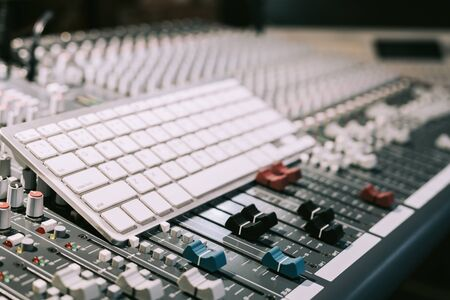 white keyboard on audio mixing console, computer in digital recording, broadcasting technology concept